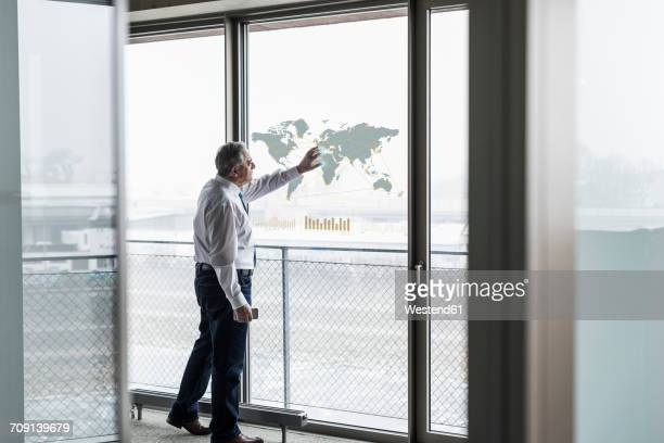 Businessman touching windowpane with world map in office