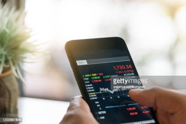 businessman trading stocks with smarthphone and check stock market data - devolución del saque fotografías e imágenes de stock