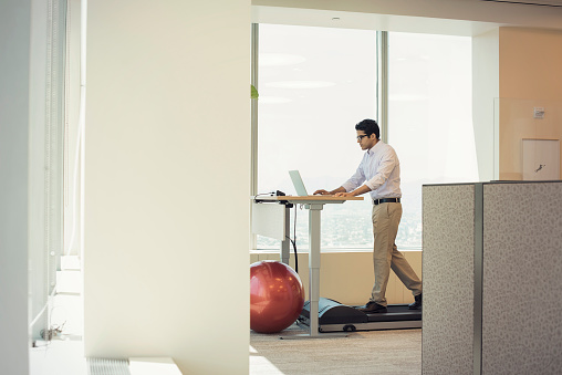 Businessman training on tread mill while using laptop - gettyimageskorea