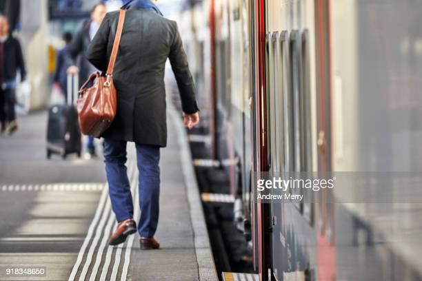 Businessman, traveler on platform boarding a train at Zurich Central Station