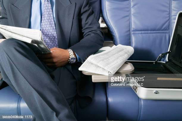 businessman traveling in am airplane - mid section stock photos and pictures