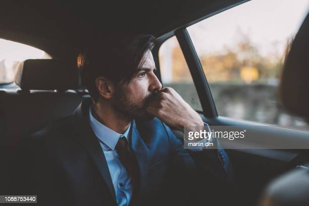 businessman traveling in taxi - formal businesswear stock pictures, royalty-free photos & images