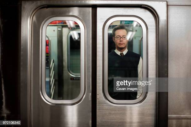 businessman traveling in train seen through vehicle door - subway train stock pictures, royalty-free photos & images