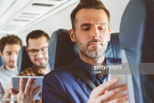 Businessman travelling by flight using smart phone
