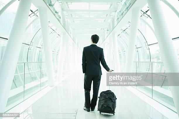 Businessman travelling down a glass tunnel.