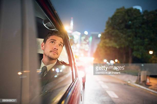 Businessman travelling in a taxi at night.