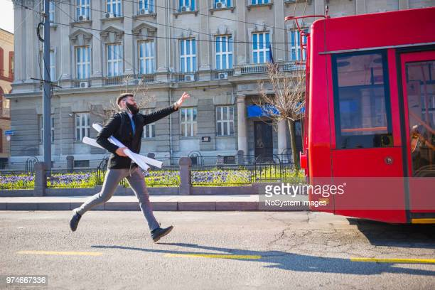 businessman trying to catch the bus - autocarro imagens e fotografias de stock