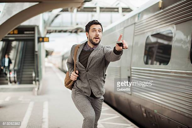 businessman trying to catch the train - urgency stock pictures, royalty-free photos & images
