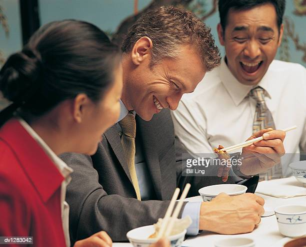 Businessman Trying to Eat Chicken Feet With Chopsticks in a Chinese Restaurant