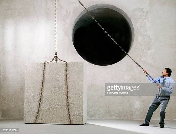 Businessman Trying to Lift Cube Into Round Hole