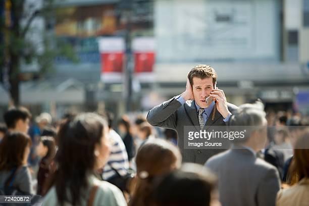 Geschäftsmann versucht ein Handy zu hören