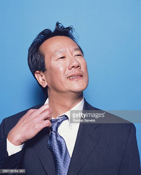 Businessman trying to loosen collar and tie, portrait