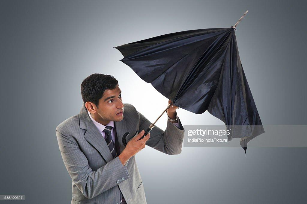 Businessman trying to open umbrella : Stock Photo
