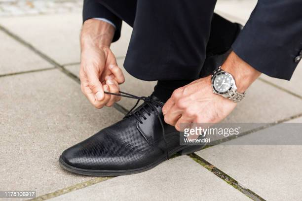 businessman tying his shoe on pavement, close-up - calzature di pelle foto e immagini stock