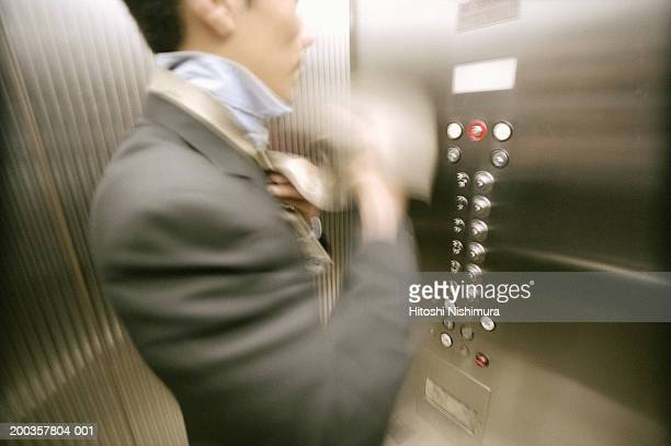Businessman tying necktie in elevator, mid section (blurred motion)