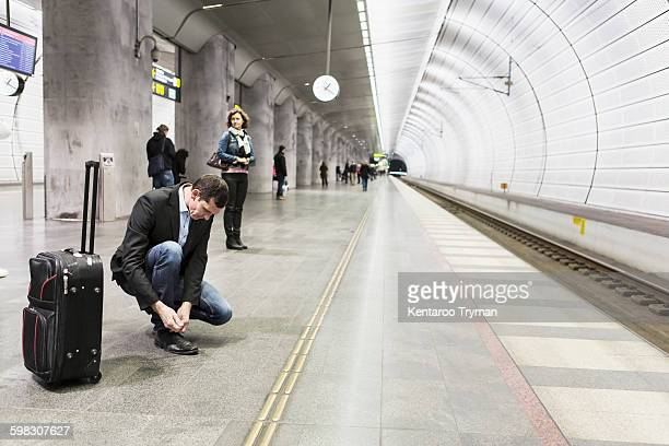 Businessman tying shoelace while waiting at railway station