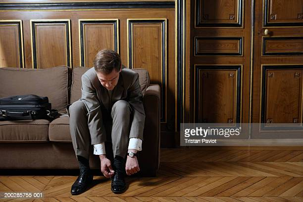Businessman tying shoelaces, sitting on sofa in panelled room