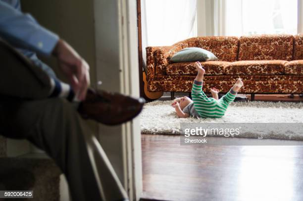 Businessman tying shoes as son plays in livingroom