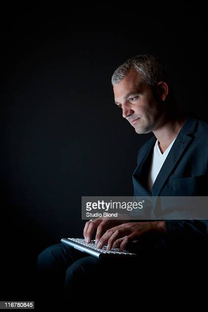 a businessman typing on a computer keyboard in the dark - regarder vers le bas photos et images de collection