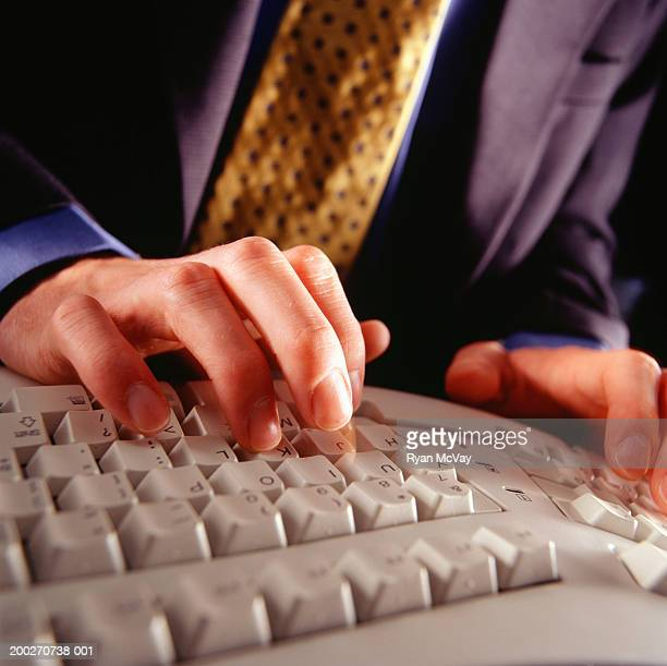 Businessman typing on ergonomic keyboard, close-up of hands