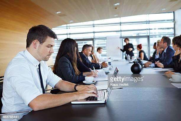 Businessman typing on laptop at big presentation