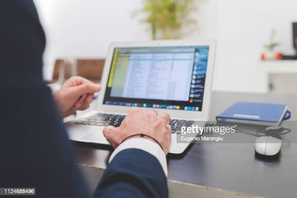 businessman typing on laptop at office desk, over shoulder view - over the shoulder view stock pictures, royalty-free photos & images