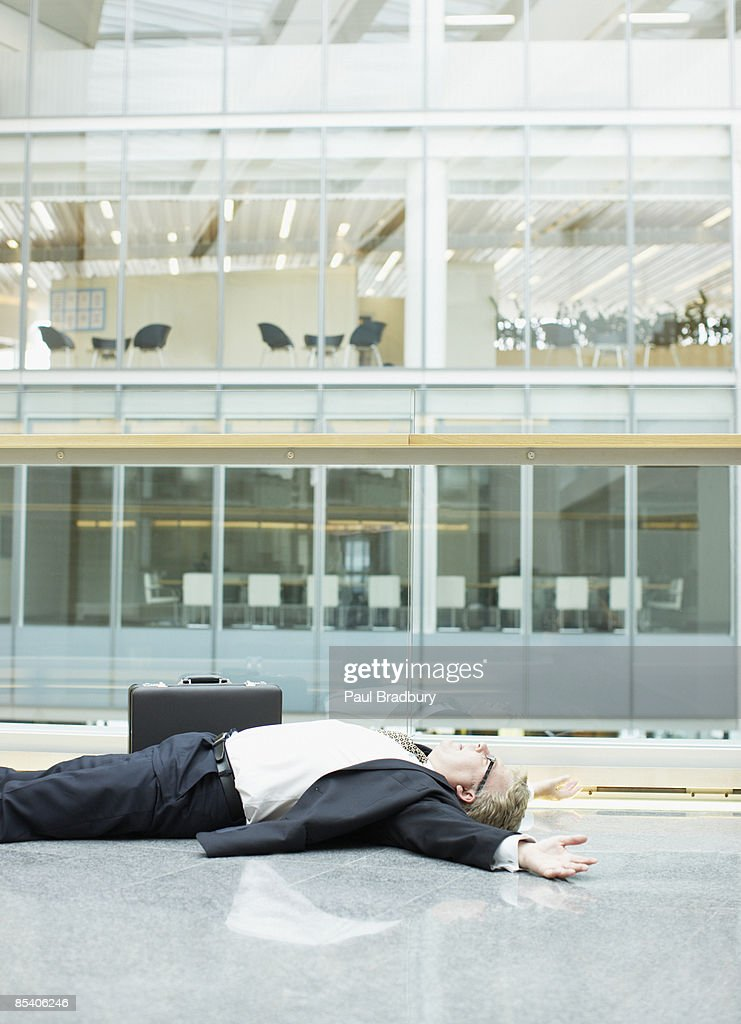 Businessman unconscious in building lobby : Stock Photo