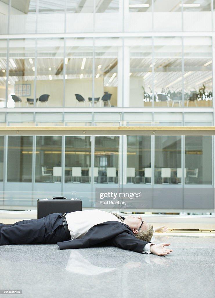 Empresário inconsciente no Átrio do edifício : Foto de stock