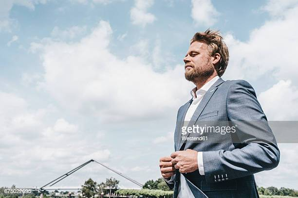 Businessman under sky with clouds