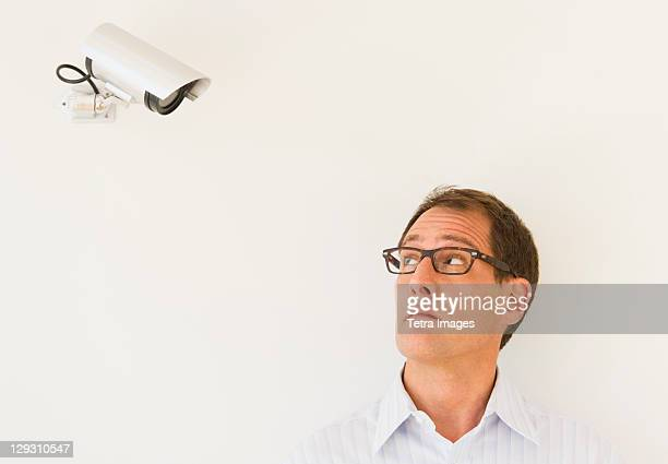 businessman under surveillance of security camera - big brother orwellian concept stock pictures, royalty-free photos & images