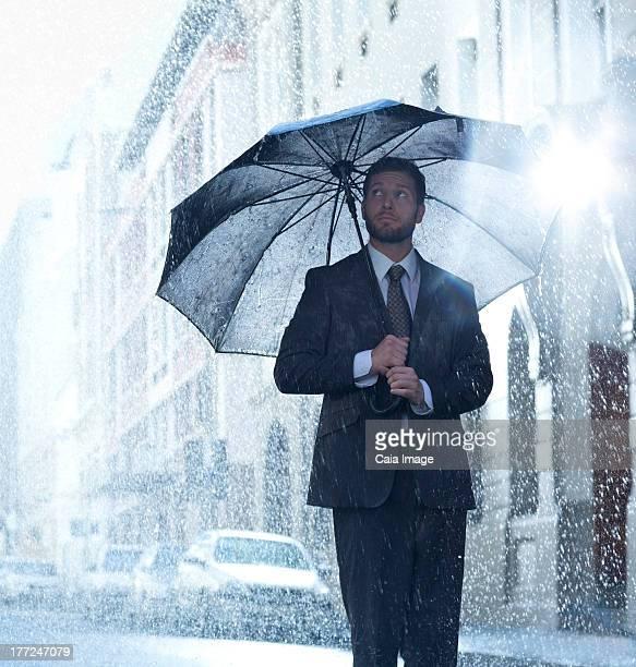 Businessman under umbrella in rainy street
