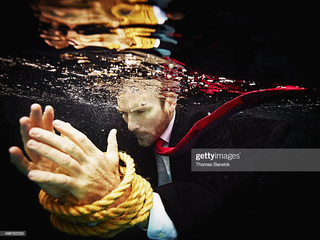 Businessman underwater with hands tied : Stock Photo