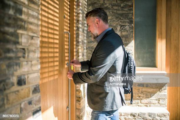 businessman unlocking the front door - open backpack stock pictures, royalty-free photos & images