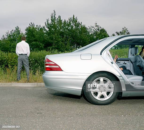 Businessman urinating at side of road by car, rear view