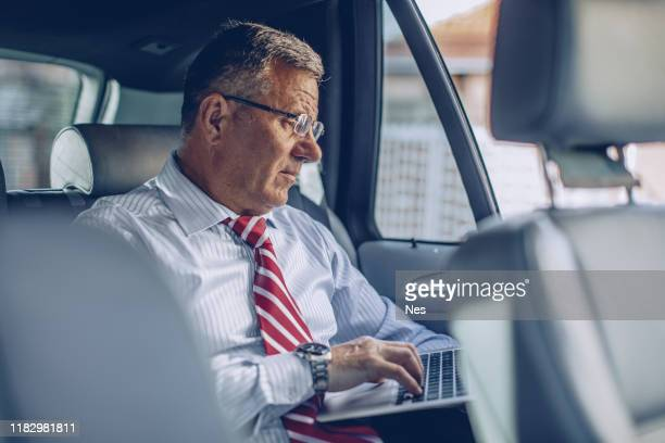 a businessman uses a laptop in the back seat of a moving car - ascot stock pictures, royalty-free photos & images