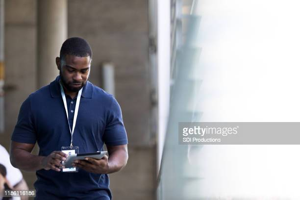 businessman uses digital table while walking outside the office building - identity card stock pictures, royalty-free photos & images