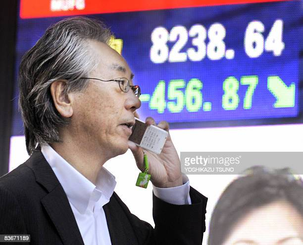 A businessman uses his mobile phone in front of a share prices board in Tokyo on November 13 2008 Japan's share prices fell 45687 points to close at...