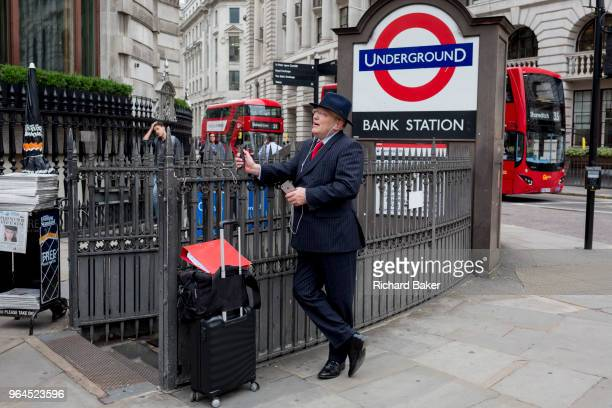 A businessman uses his mobile phone outside the entrance of Bank Underground Station at the corner of King William Street in the City of London on...