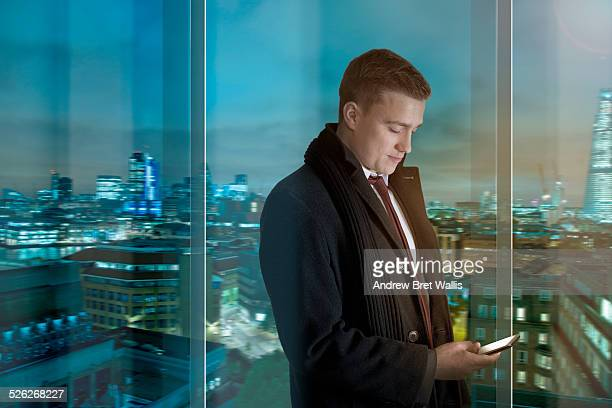 Businessman uses smart phone overlooking the city