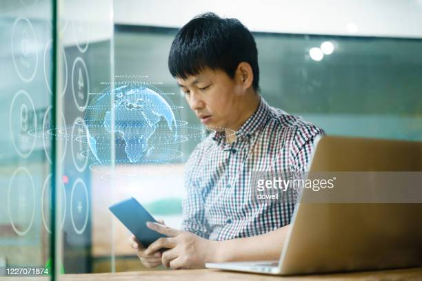 businessman uses virtual visual screen to work in office - east asian ethnicity stock pictures, royalty-free photos & images