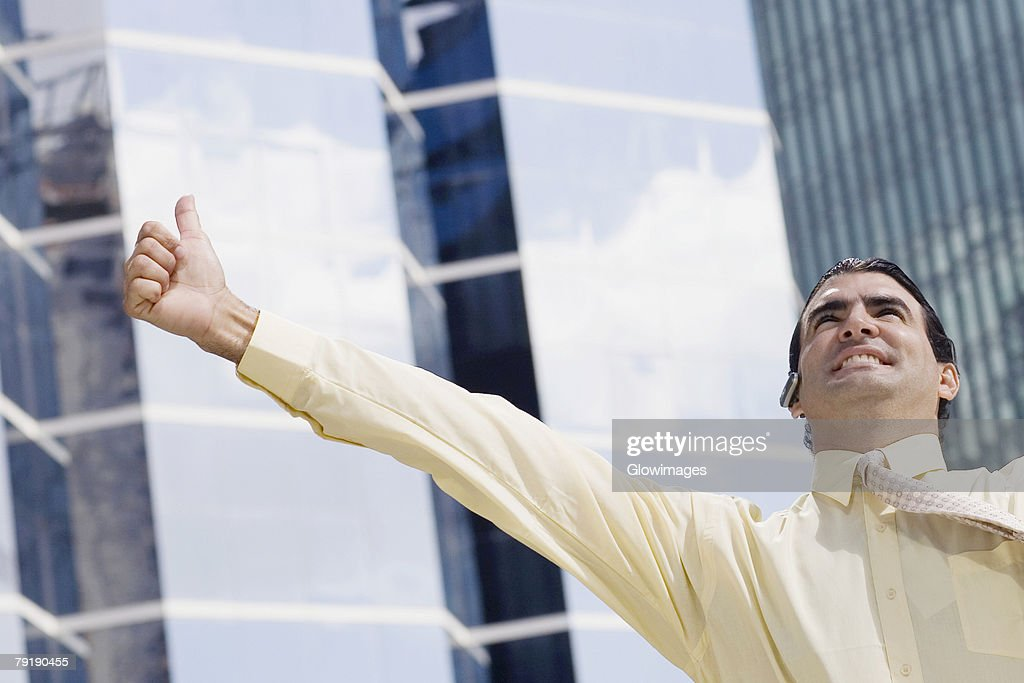 Businessman using a bluetooth device and making a thumbs up sign : Foto de stock