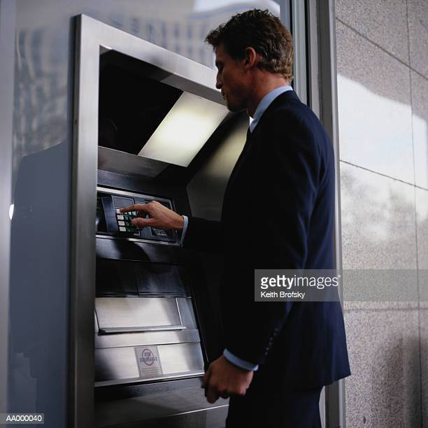businessman using a cash machine - pin stock pictures, royalty-free photos & images