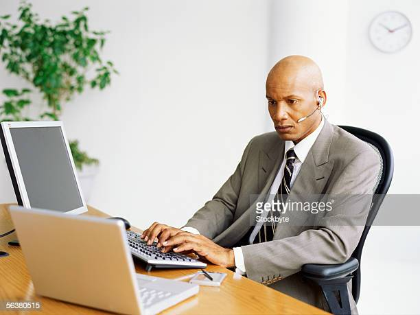 businessman using a computer wearing a headset