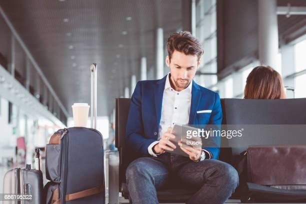 空港の待合室でデジタル タブレットを使用するビジネスマン