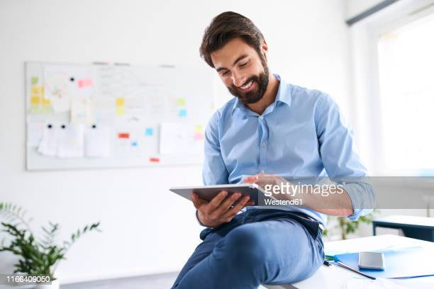 businessman using a digital tablet in his office - gifted movie stock pictures, royalty-free photos & images