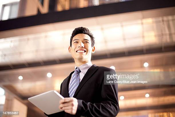 A businessman using a digital tablet outside an office building at night