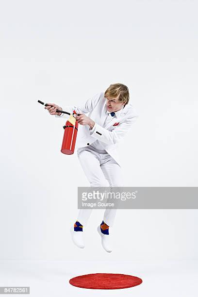 A businessman using a fire extinguisher
