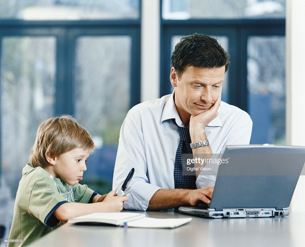 Businessman Using a Laptop and His Son Holding a Pen : Stock Photo