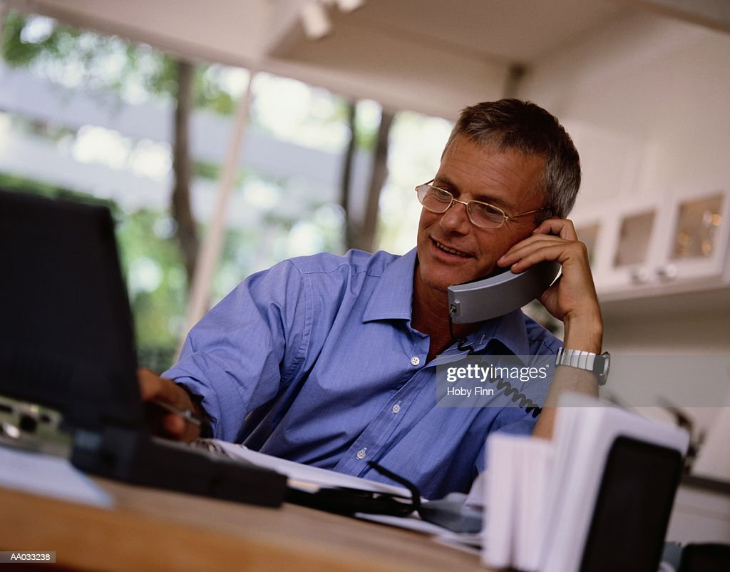 Businessman Using a Laptop and Talking on a Phone : Stock Photo