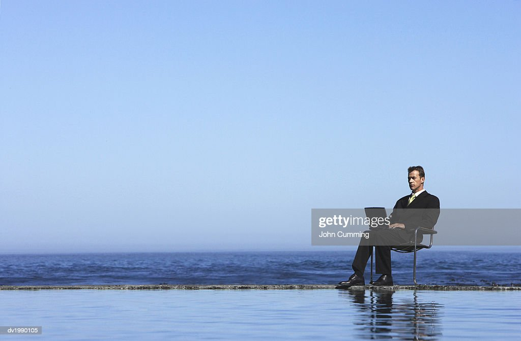 Businessman Using a Laptop Computer by the Sea : Stock Photo